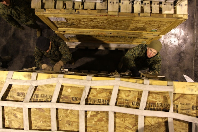 TRONDHEIM, Norway- Staff Sergeant Joseph Conradi, embark specialist, Marine Forces, Europe  and MSgt. Steven Albanese, facilities chief, Marine Forces, Europe secure the cargo straps on a pallet, while assembling a shipment of sustainment equipment headed to the Republic of Georgia to support the Georgia Deployment Program. During the course of three days a team of five Marines from Marine Forces, Europe, II Marine Expeditionary Force and two airmen from the 819th Red Horse Squadron  assembled 14 pallets of gear, set to be delivered to training areas in the Republic of Georgia.  The shipment contained tents, a shower system, tool kits, generators, fuel bladders and host of other items, intended to help the Marines and their Georgian counterparts, to enhance the living conditions in training areas in the Republic of Georgia.