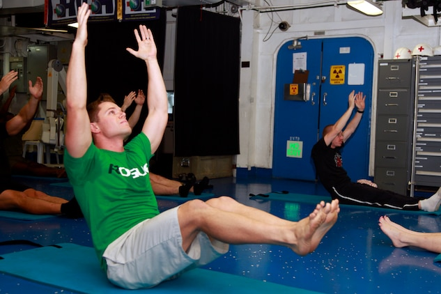 Capt. Matt T. Davis, AH-1Z pilot, Marine Medium Helicopter Squadron 364 (Rein.), 15th Marine Expeditionary Unit, performs a Pilates exercise during a PITAIYO class in the medical facility aboard the USS Peleliu, Dec. 7. PITAIYO, an acronym for put it together all in your orbit, is a fusion of Pilates, Tai-chi, and yoga blended into one class. It is designed to increase core strength, flexibility, balance and coordination. The class is another opportunity Marines and sailors have to allow their minds to decompress from the stresses of deployment. The 15th MEU is deployed as part of the Peleliu Amphibious Ready Group as a U.S. Central Command theater reserve force, providing support for maritime security operations and theater security cooperation efforts in the U.S. 5th Fleet area of responsibility. Davis, 26, is from Viera, Fla. (U.S. Marine Corps photo by Cpl. John Robbart III)