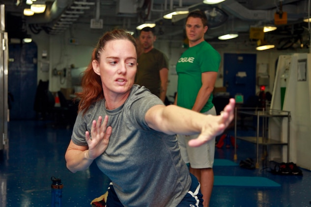 Gunnery Sgt. Jennifer M. Antoine, PITAIYO instructor and the public affairs chief, 15th Marine Expeditionary Unit, teaches movements during a PITAIYO class in the medical facility aboard the USS Peleliu, Dec. 7. PITAIYO, an acronym for put it together all in your orbit, is a fusion of Pilates, Tai-chi, and yoga blended into one class. It is designed to increase core strength, flexibility, balance and coordination. The class is another opportunity Marines and sailors have to allow their minds to decompress from the stresses of deployment. The 15th MEU is deployed as part of the Peleliu Amphibious Ready Group as a U.S. Central Command theater reserve force, providing support for maritime security operations and theater security cooperation efforts in the U.S. 5th Fleet area of responsibility. Antoine, 39, is from Altoona, Wis. (U.S. Marine Corps photo by Cpl. John Robbart III)