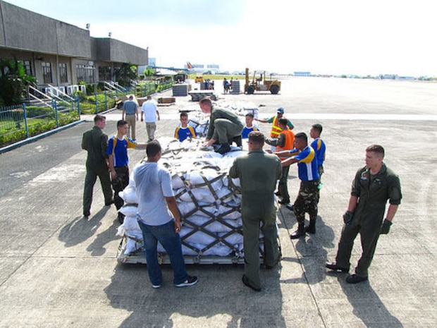 U.S. and Philippine service members load food packs destined for disaster-impacted areas in the southern Philippines, Dec. 9, 2012.