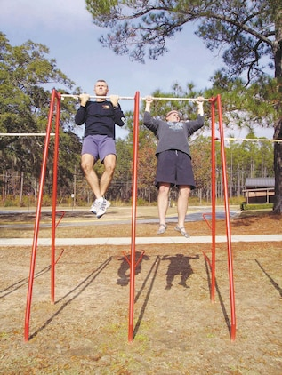 Maj. Michael Mullins and Chief Warrant Officer 3 Stephen Sutton practice pull-ups recently.