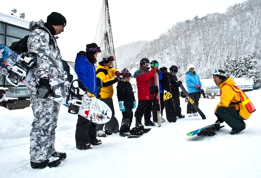 HAKUBA, Japan. -- Takashi Yoshii, 374th Force Support Squadron Outdoor Recreation tour guide, leads a group of amateur snowboarders away from a ski-lift ticket booth Dec. 12, 2012, during a ski trip. Yoshii has been snowboarding for more than 17 years and led a snowboarding course that taught basic skills to Yokota community members.  (U.S. Air Force photo/Senior Airman Cody H. Ramirez)
