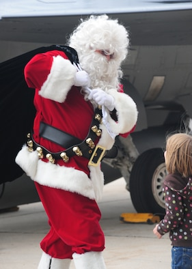 Santa is greeted by a child after he gets out of an F-16 Fighting Falcon fighter jet at Hill Air Force Base, Utah, for the annual 388th Fighter Wing holiday party Dec. 8. (U.S. Air Force photo by Kim Cook/Released).