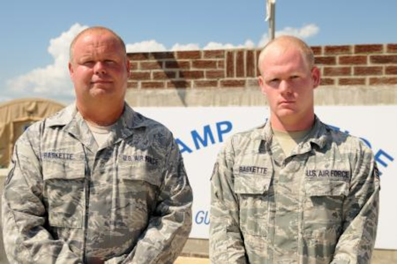 Air Force Master Sgt. Richard Dale Baskette and his son Senior Airman Richard Grant Baskette Jr. pose in front of Camp Justice in Guantanamo Bay, Cuba, Nov. 6. (U.S. Army photo by Sgt. Ryan Hallock/Released).