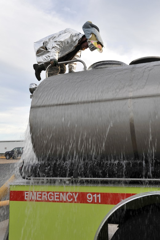Airman 1st Class William Lawrence, Team Whiteman firefighter, climbs the back of a tanker to simulate a water re-supply operation Dec. 5 at Whiteman Air Force Base, Mo. The team is required to conduct upgrade training and exercises throughout the year to keep their skills up-to-date and mission-ready. (U.S. Air Force photo/Heidi Hunt) (Released)