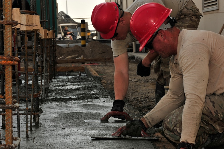 SOUTHWEST ASIA -- U.S. Air Force Senior Airman Tyler Vann, 560th RED HORSE Squadron structures journeyman, and Senior Airman John Fox, 560th RHS DIRTBOY, smooth recently poured concrete Dec. 4, 2012.  RED HORSE is comprised of specialized Airmen in 21 trades who deploy to austere and existing bases to build new facilities. (U.S. Air Force photo/Tech. Sgt. Christina M. Styer) (RELEASED)