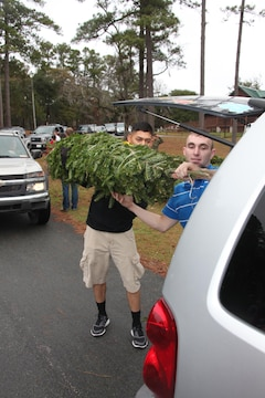 Lance Cpl. Randy Webb, left, and Sgt. Patrick Kennedy, right, work on putting a Christmas tree into the back of a vehicle during the 2012 Trees for Troops event at Hancock Marina Dec. 10. The Marines who volunteered unloaded two FedEx trailers with hundreds of trees on each, all donated by a Massachusetts tree farm. Both Marines are with Marine Wing Communications Squadron 28.