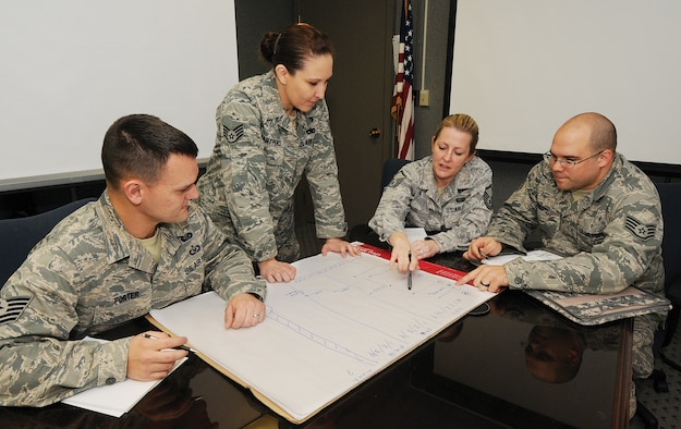 """Air Force manpower analysts of the 5th Manpower Requirements Squadron review findings to aid them in developing manpower standardization for an organization. Tech. Sgt. Richard Porter, Staff Sgt. Autumn Hartpence, Master Sgt. Tara Ward and Staff Sgt. Nickolas Swartz, from left, are four of the 37-member squadron based at Tinker who thoroughly review organizations Air Force-wide. """"Our studies give them (organizations) a means to justify their requirements,"""" said Sergeant Porter. (Air Force photo by Margo Wright)"""