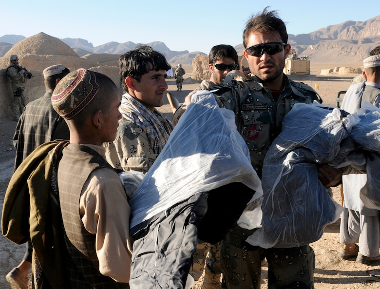 Lt. Abdul Azim Nooree, an officer with the Afghan Border Police, hands out blankets and clothing to children in the village of Gagre Naw, Afghanistan, during Operation Southern Strike IV, Nov. 18, 2012. More than 4,400 pounds of flour, rice, blankets and clothing were delivered to remote villages in Spin Boldak and Tak-the Pol Districts by Afghan Air Force Kandahar Air Wing Mi-17 helicopter crew members and the Afghan Border Police. (U.S. Army Photo/Staff Sgt. Ryan Sheldon)