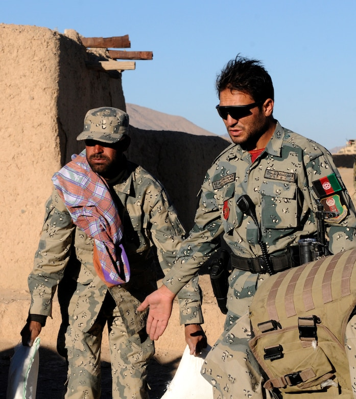 Lt. Abdul Azim Nooree (right), an officer with the Afghan Border Police, assists handing out humanitarian aid in the village of Gagre Naw, Afghanistan, during Operation Southern Strike IV, Nov. 18, 2012. (U.S. Army Photo/Staff Sgt. Ryan Sheldon)