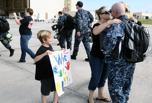 Aviation structural mechanic Chief Petty Officer Chad Burg, Helicopter Sea Combat Squadron TWO FIVE, embraces his wife upon his return from the USNS Amelia Earhart at Andersen Air Force Base, Guam, Dec. 13,2012. While aboard the Earhart, the detachment moved 3 million pounds of ordnance and cargo, supporting 37 missions and totaling 322 flight hours. Detachment ONE conducted vertical replenishment operations in support of Commander, Task Force 73 while offering logistics and search and rescue support. (U.S. Air Force photo by Airman 1st Class Mariah Haddenham / Released)