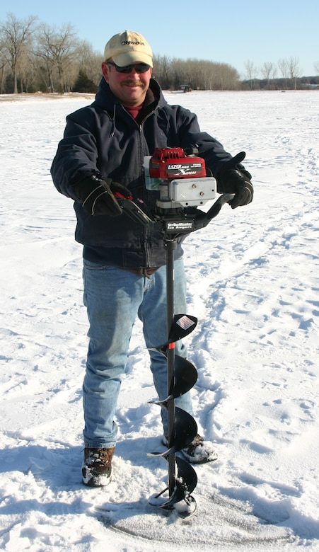 Man drilling a hole for ice fishing.
