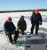 Theee men ice fishing.