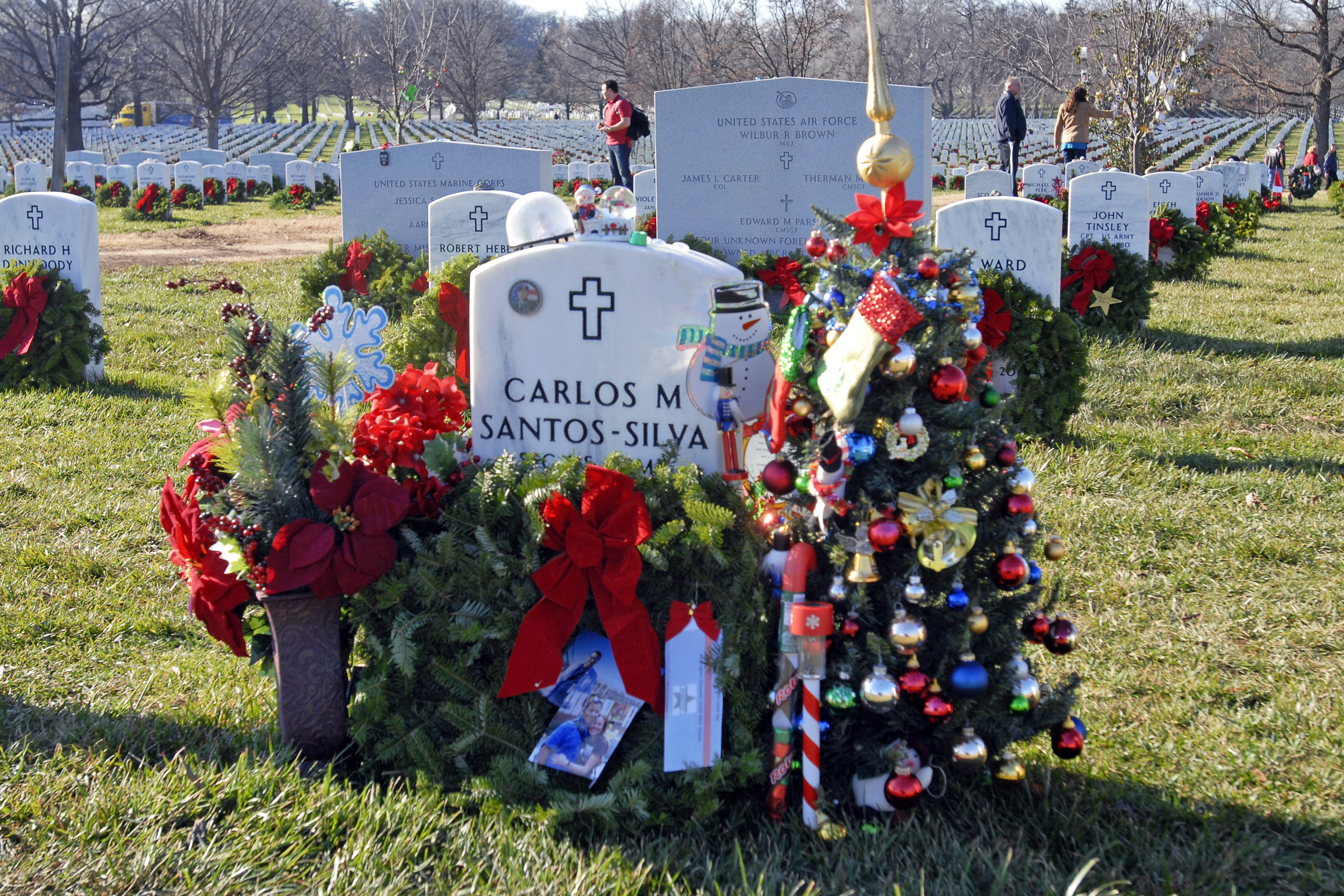 a wreath flowers and a small christmas tree are placed at the grave marker of