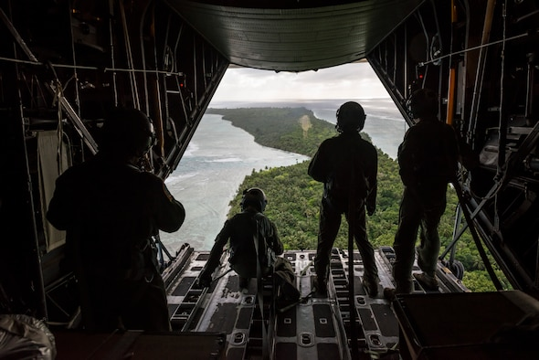 OVER THE PACIFIC OCEAN -- Loadmasters and aircrew from the 36th Airlift Squadron look out over a drop zone after delivering humanitarian bundles to the island of Ulal as part of Operation Christmas Drop, Dec. 11, 2012. Due to the additional donations received that year, riggers with the 374th Logistics Readiness Squadron had to adjust the way the bundles were built, making it possible to drop more supplies than ever before, and achieving a 100 percent success rate with the adjusted rigging. (U.S. Air Force photo by Tech. Sgt. Samuel Morse)