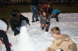 Volunteers helping children make snowmen.
