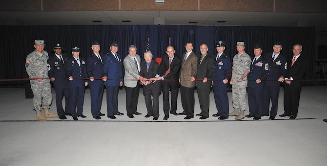 Retired Chief Master Sgt. Robert Gaylor, the fifth chief master sergeant of the Air Force (with scissors) and keynote speaker for the event, along with senior leaders, members of Richard Etchberger's family and construction officials get ready to cut the ribbon to open the Airman Training Complex #1. (US Air Force Photo by Mr. Alan Boedeker)