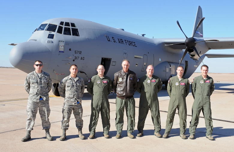 Members of the 317th Airlift Group pose for a group photo with Maj. Gen. William J. Bender, U.S. Air Force Expeditionary Center commander, after delivering the 317th AG's newest C-130J Dec. 13, 2012, at Dyess Air Force Base, Texas. This is the 24th C-130J of 28 to be delivered to Dyess by 2013, replacing the legacy fleet of C-130Hs. Once the final aircraft is delivered, Dyess will be home to the largest C-130J fleet in the world.  (U.S. Air Force photo by Airman 1st Class Peter Thompson/Released)