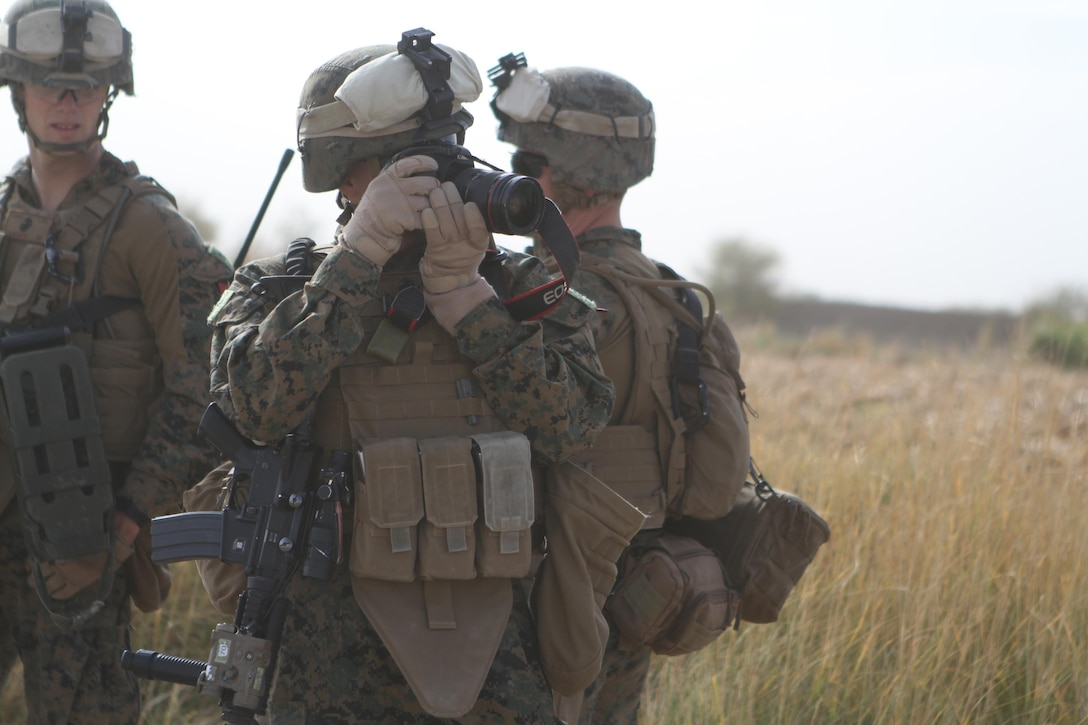 Lance Cpl. Robert Walters, combat photographer, 3rd Battalion, 9th Marine Regiment, Regimental Combat Team 7, takes a photograph while on a patrol through the battalion's area of operations, Nov. 11, 2012. Walters broke his elbow a year and a half before he joined the Marine Corps and refused to let it hinder him as a Marine.