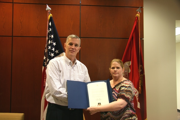 Andrew Dwyer, Program Manager for Global Combat Support Systems-Marine Corps, presents Amy Mersereau-Cooper with the President's Volunteer Service Award, Dec. 7th, 2012. This is Mersereau-Cooper's second award, making her a Bronze-level award recipient.