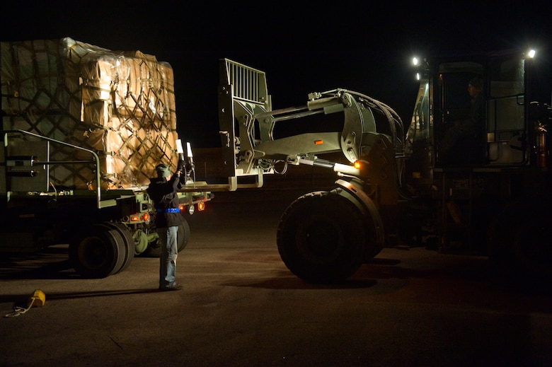 BUCKLEY AIR FORCE BASE, Colo. – Christopher Henriques, 460th Logistics Readiness Squadron, directs Staff Sgt. Steven Bouquet, 460th LRS, while loading a pallet of humanitarian supplies Dec. 14, 2012, at the 460th LRS building. More than 17,000 pounds of household goods, medical supplies and equipment was loaded onto C-130J Hercules from the 317th Airlift Group, Dyess Air Force Base, Texas. (U.S. Air Force photo by Airman 1st Class Riley Johnson)