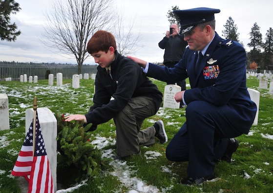 Col. Brian Newberry, 92nd Air Refueling Wing commander, and his son Matthew lay a wreath on a veteran's headstone Dec. 15, 2012, during the Wreaths Across America event at the Fort Wright Cemetery in Spokane, Wash. This marks the first year that Wreaths Across America was held at the cemetery. (U.S. Air Force photo by Airman 1st Class Taylor Curry)