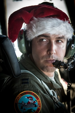 OVER THE PACIFIC OCEAN -- Capt. Dereck Monnier, 36th Airlift Squadron pilot and aircraft commander, looks at a fellow crew member during a flight over Micronesia Dec. 18, 2012. Monnier wore a Santa hat because the flight was part of Operation Christmas Drop, a 61-year-old humanitarian airlift mission carrying donated supplies to remote islands in Micronesia. (U.S. Air Force photo by Tech. Sgt. Samuel Morse)
