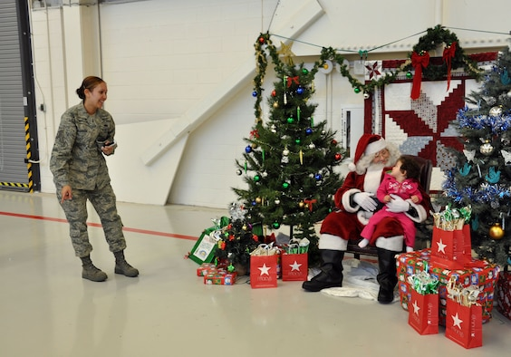 NELLIS AIR FORCE BASE, Nev. -- (Far left) Tech. Sgt. Jennifer Orozco, 926th Aircraft Maintenance Squadron Commander's Support Staff, encourages her daughter to tell Santa what she wants for Christmas at the Flanker hangar here Dec. 8. Santa's visit was part of an annual holiday party hosted by the base's Reserve and Regular Air Force maintenance units. (U.S. Air Force photo/Maj. Jessica Martin)