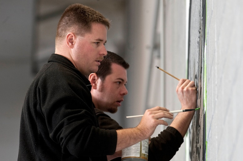 Staff Sgt. Daniel Sullivan, 823rd Maintenance Squadron aircraft structural maintenance craftsman, and Michael Sullivan, artist and brother of Sergeant Daniel Sullivan, apply a coat of paint to the new 823rd MXS unit patch Dec. 15, 2012, at Nellis Air Force Base, Nev. Sergeant Sullivan has had experience painting aircraft as part of a corrosion control process and has painted several murals in Southwest Asia. (U.S. Air Force photo by Staff Sgt. Christopher Hubenthal)