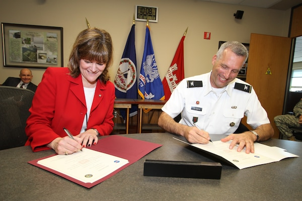 Cathy Mangum, director of center operations for NASA Langley Research Center, and Col. Paul Olsen, Norfolk District commander, sign a proclamation announcing a master support agreement between the two agencies for planning, design, engineering, project management, real estate and other engineering support services as required by the center. The agreement allows NASA Langley to reach out to the Corps of Engineers in a streamlined process; saving the center money and time.  (U.S. Army photo/Patrick Bloodgood)