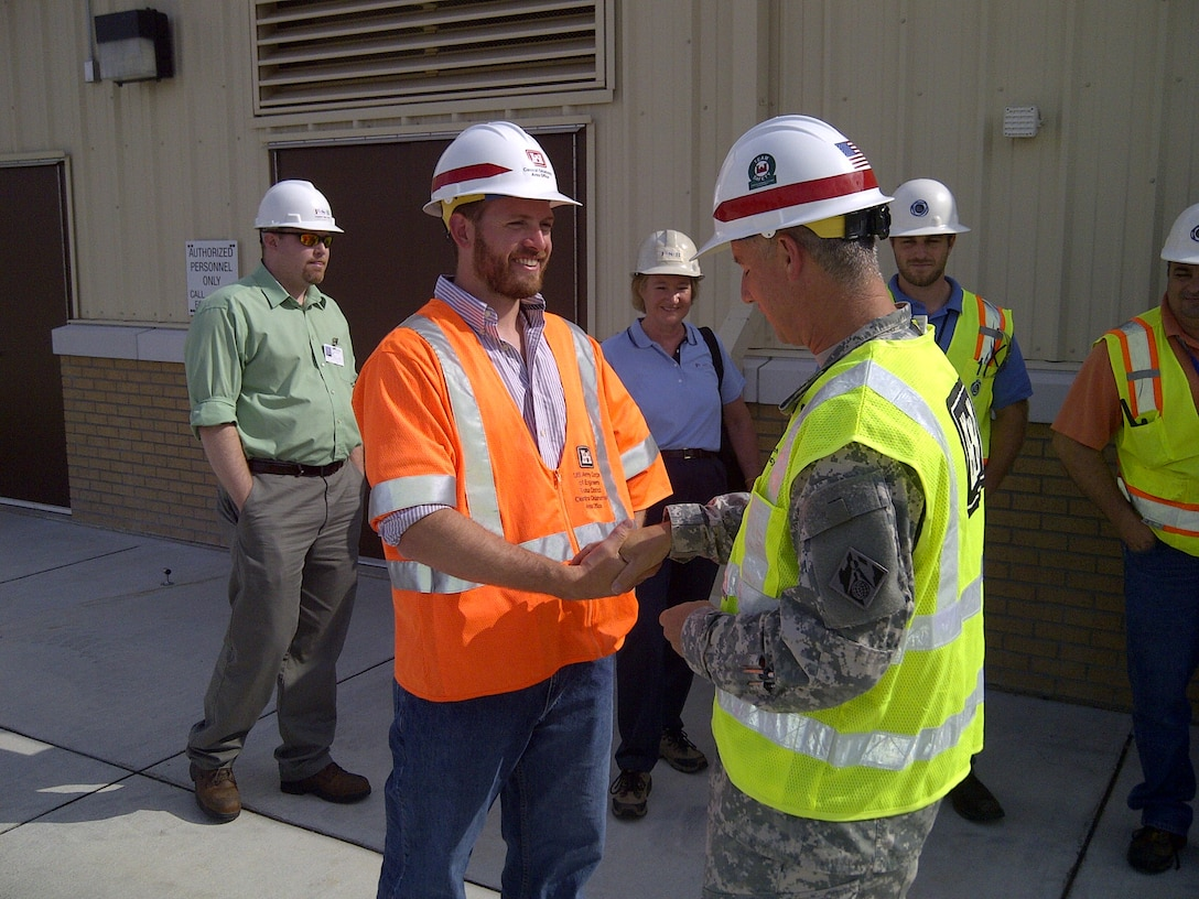 Matthew C. Polley, EIT Fire protection engineer, shakes hands with the Tulsa District Commander after a hangar high expansion foam dump test.