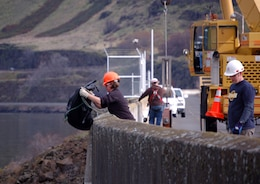 Corps of Engineers and Wash. Department of Fish and Wildlife employes dewater The Dalles Dam fish ladder. Fish remaining in the ladder are collected and returned to the Columbia River.
