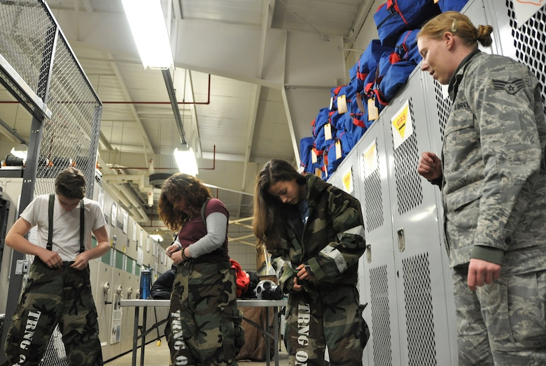 Senior Airman Katherine Anderson (right), 51st Civil Engineer Squadron emergency management journeyman, goes through proper wear of MOPP gear with students from the 10th grade Osan High School chemistry class that visited the emergency management flight Dec. 14, 2012. The field trip was coordinated to provide a hands-on instructional lesson about chemical warfare.  (U.S. Air Force photo/Senior Airman Kristina Overton)