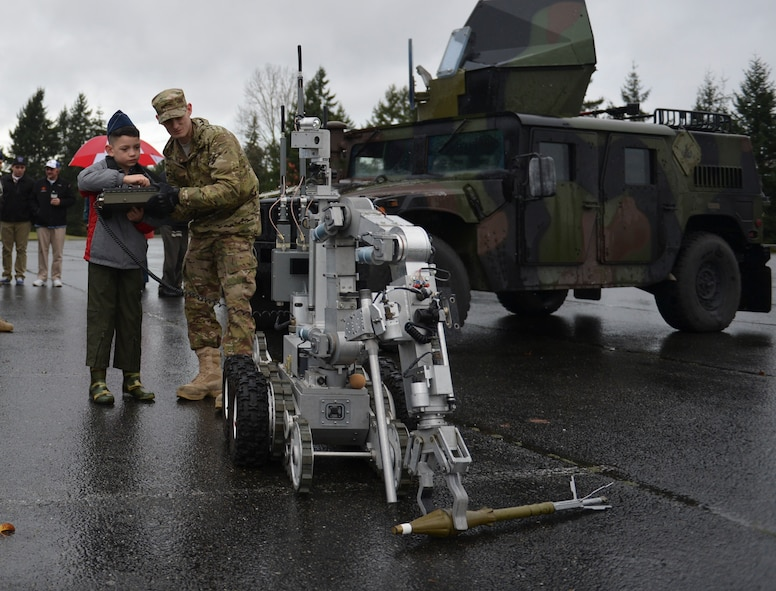Tommy McGraw operates an explosive ordnance disposal robot with the help of Airman 1st Class Christopher Benefield, 627th Civil Engineer Squadron EOD technician, Dec. 17, 2012, at Joint Base Lewis-McChord, Wash. Tommy used the robot to pick up an inert rocket-propelled grenade. (U.S. Air Force photo/Staff Sgt. Jason Truskowski)