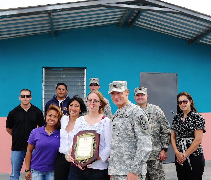 Representatives from Joint Task Force-Bravo pause for a photo in front of one of the houses they helped construct over five weeks after the ribbon cutting ceremony November 28, 2012. More than 100 servicemembers volunteered time to build 14 houses in the community of Cane, Honduras near Soto Cano Air Base.(U.S. Air Force photo/Capt. Rebecca Heyse)