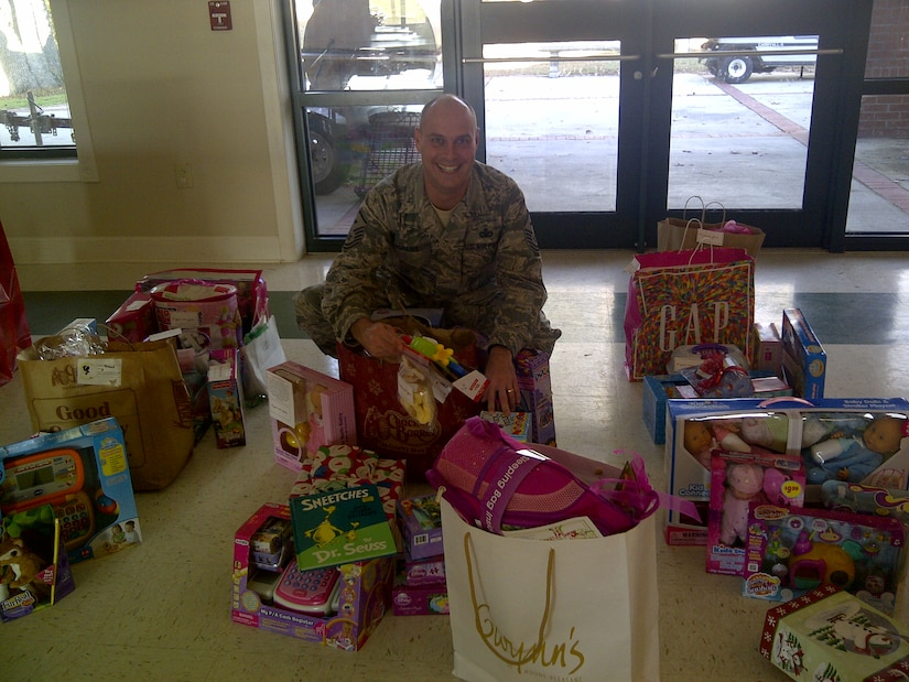 Master Sgt. Brent Hopkins, 437th Operations Support Squadron first sergeant, displays the gifts donated to the Joint Base Charleston Angel Tree program  Dec. 14, 2012 at the Chapel Annex at JB Charleston – Air Base, S.C. The program raised more than 300 gifts for military children whose families may be facing financial hardships this holiday season. (Courtesy photo)