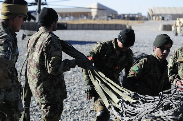 Pathfinder students from 4th Kandak, 2nd Brigade, 205th Corps, prepare equipment to be attached to the bottom of an Afghan Air Force Kandahar Air Wing Mi-17 helicopter during the 4th Lightning Strike Pathfinder Academy, where the students were trained and certified as Pathfinders by Afghan instructors in partnership with Pathfinders of Company F, 2nd Battalion, 25th Aviation Regiment, 25th Combat Aviation Brigade, at Forward Operating Base Wolverine, Afghanistan, Dec. 5th. (Photo by Capt. Richard Barker, 25th Combat Aviation Brigade Public Affairs)