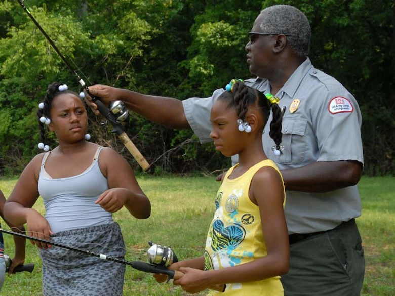 Park Ranger Robert Davis helps Aniya Young (Left), 8, and Unique Henderson, 10, with their fishing poles during a fishing rodeo held June 14, 2011 at Cook Recreation Area located at J. Percy Priest Lake in Hermitage, Tenn.  The kids from the Hermitage Community Center enjoyed a day of fishing and learned about water safety. (USACE photo by Michael Rivera)