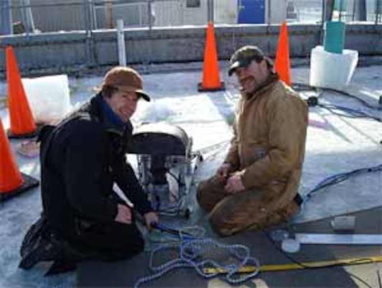 Scientist Dr. Jeremy Wilkinson, Scottish Association for Marine Science, left, and ERDC-CRREL's Bill Burch prepare the submersible trolley for testing within CRREL's Geophysical Research Facility. Attached to the trolley's structure are a suite of sensors that includes cameras, lasers and sonars, in an attempt to detect and map an oil spill from under the ice.