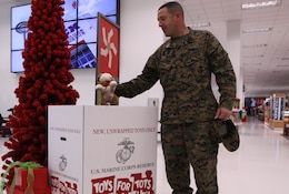 Master Gunnery Sgt. Gary S. Teicher, the ordnance Chief for 1st Marine Division here, places a stuffed animal into a toy donations box at the Marine Corps Exchange here, Dec. 20. Toys for Tots collects donations from October to December, and will reach an estimated 60,000 local, needy children this holiday season.