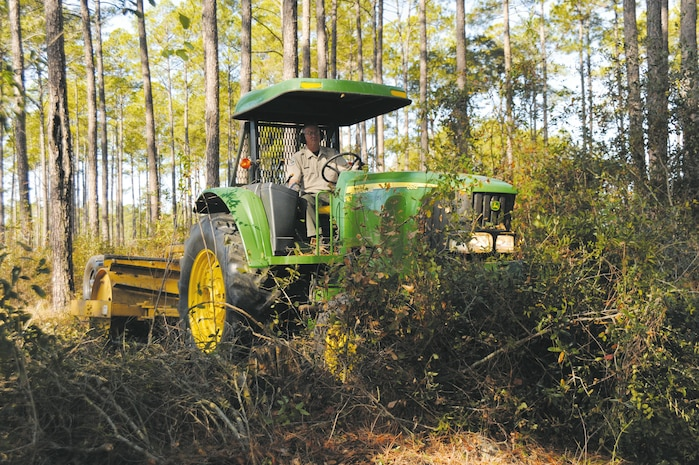 Game Warden Al Belanger, operates a 12,500-pound drum chopper hooked to a tractor to cut down dense underbrush near Production Plant Albany before prescribed burning begins aboard Marine Corps Logistics Base Albany.