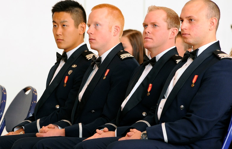 From left to right: Cadets 1st Class Jonathan Yi, Erik Soderberg, Connor Dietz and Raymond Crone III receive their diplomas in a winter graduation ceremony held Wednesday in Arnold Hall. Academy Superintendent Lt. Gen. Mike Gould encouraged the newly commissioned officers to strive to be leaders of vision and character. (U.S. Air Force photo/Mike Kaplan)