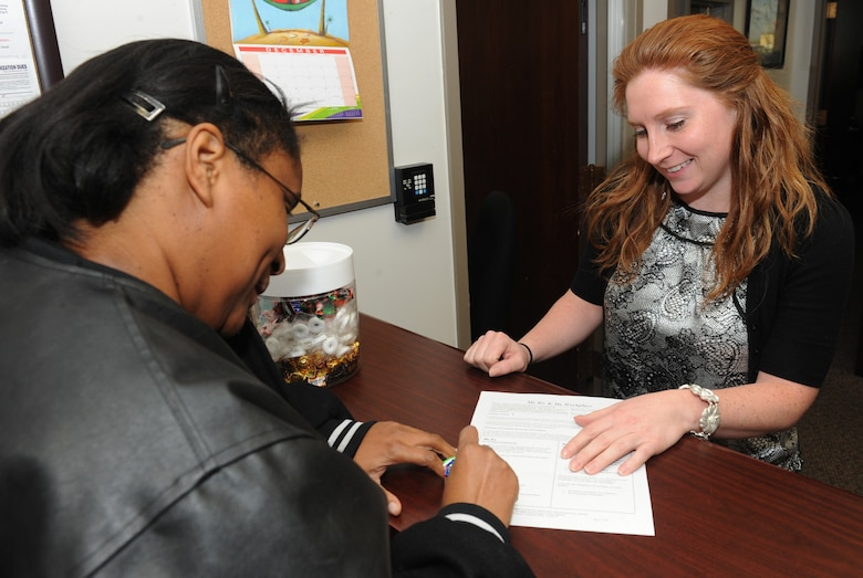 Chrystal Hampton, 509th Force Support Squadron human resources assistant, helps a customer fill out a form at the civilian personnel office, Dec. 10 at Whiteman Air Force Base, Mo. The team's employee management and labor relations section handles issues concerning bargaining unit employees, the installation's Labor Management Agreement, benefits, leave and employee conduct.