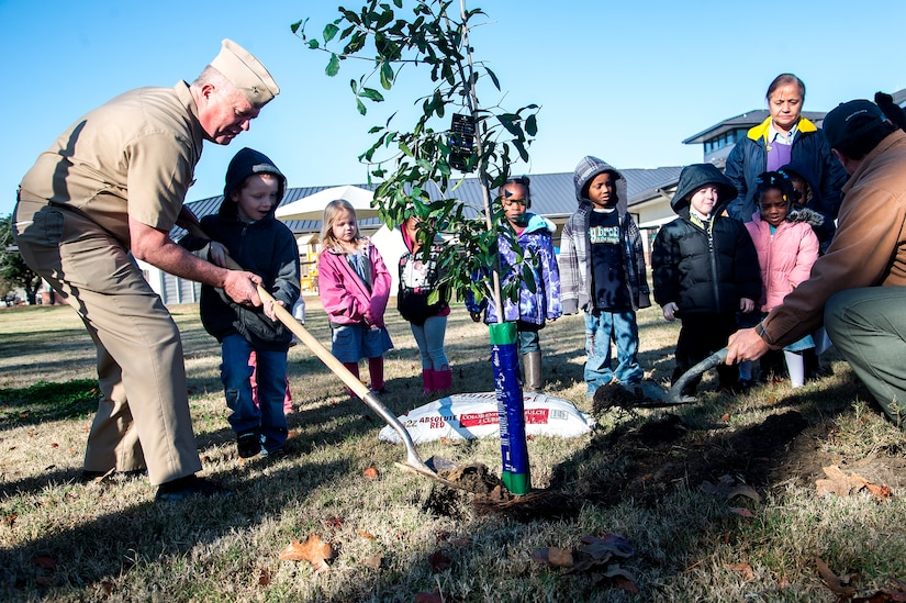 Capt. Thomas Bailey, Joint Base Charleston deputy commander and Keith Thompson, JB Charleston conservation program manager, along with kids from the General Thomas R. Mikolajcik Child Development plant a tree on Arbor Day on Dec. 14, 2012, at Joint Base Charleston - Air Base, S.C. This is the 17th year JB Charleston has been a member of the Tree City USA foundation. To become a Tree City USA member, a community must meet four annual standards: must be a tree protection board or manager, a tree care ordinance, a comprehensive community forestry program, and an Arbor Day observance. (U.S. Air Force photo/Staff Sgt. Rasheen Douglas)