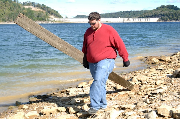 Rob Baulsir, U.S. Army Corps of Engineers Nashville District employee and Leadership Development Program student, carries out a board he found on the shoreline of Center Hill Lake during a National Public Lands Day volunteer event Oct. 1, 2011. (USACE photo by Leon Roberts)