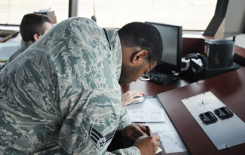 U. S. Air Force Senior Airman Cordney Stewart, 366th Operations Support Squadron air traffic controller, writes down information while working ground control Dec. 13, 2012, at Mountain Home Air Force Base, Idaho. Stewart communicates with ground support personnel and pilots in case of an emergency. (U. S. Air Force photo/Senior Airman Benjamin Sutton)