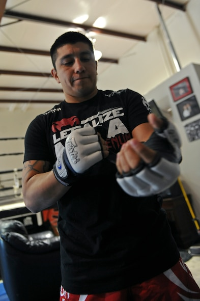 Staff Sgt. Jeremy Caudillo, 2nd Force Support Squadron fitness center supervisor, puts on a pair of mixed martial arts fighting gloves at a local MMA gym in Bossier City, La., Dec. 12. Caudillo is currently training for his first professional MMA fight in March. Caudillo competed in local amateur MMA fights for the past two years. His current record is six wins and three losses. (U.S. Air Force photo/Senior Airman Micaiah Anthony)
