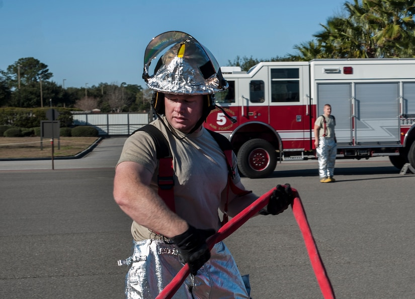 Tech. Sgt. Cory Bowers, 628th Civil Engineer Squadron firefighter, brings in a hose after a C-17  Globemaster III emergency response drill  Dec. 19, 2012, at Joint Base Charleston - Air Base, S.C. During theGlobemaster III drill, firefighters practiced for a real life situation such as a plane crash with a fire, smoke and casualties.  The drill takes place eight times a year. (U.S. Air Force photo/ Airman 1st Class Ashlee Galloway)