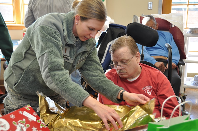 2nd Lt. Cristi Jordan, a 507th Operations Support Flight intelligence analyst helps Robert McCarthy, a veteran at the Norman Veterans Center, open a gift at the annual Christmas Party recently.  Over $4,000 was raised by members of the 507th Air Refueling Wing for gifts to be donated to the veterans.  Members of the 507th have been donating gifts since the center opened in 1996.  (Photo by Senior Airman Mark Hybers)