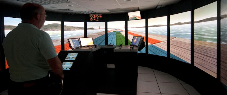 A research engineer at the helm of a Golden Gate Bridge navigation simulation at the ERDC Ship/Tow Simulator facility in Vicksburg, Miss.